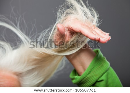Closeup  of hand of senior woman in hair. Studio shot. Isolated on grey. - stock photo