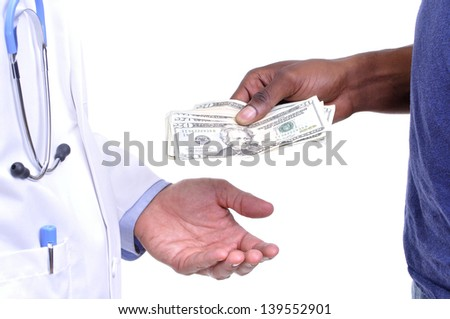 Closeup of hand of uninsured patient paying cash to hand of medical doctor wearing lab coat on white background - stock photo