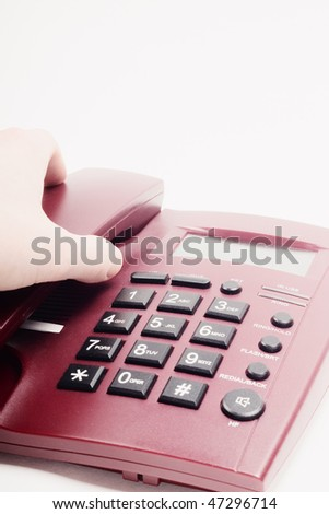 Closeup of hand picking up receiver of dark red office telephone against white background with selective focus - stock photo