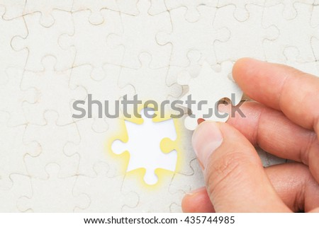 Closeup of hand placing the last jigsaw puzzle piece conceptual of problem solving, finding a solution. - stock photo