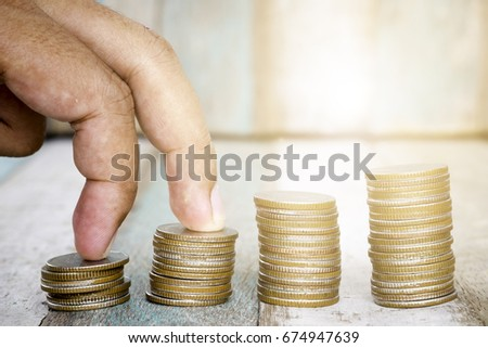 Closeup of hand put Coins to stack of coins,Concept Saving money.