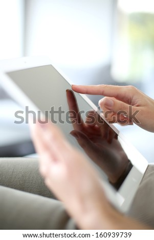 Closeup of hand sliding on digital tablet - stock photo