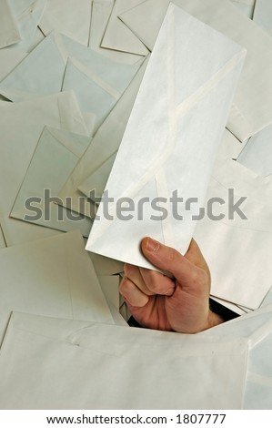closeup of hand with envelope in pile of letters - stock photo