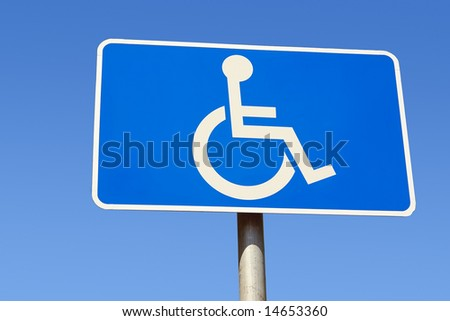 Closeup of handicapped parking place sign over blue sky - stock photo