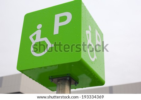 Closeup of handicapped parking place sign over rainy  sky - stock photo