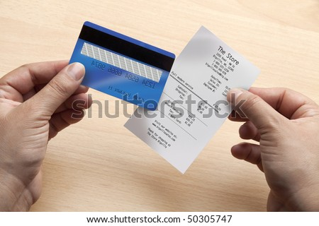 Closeup of hands holding a credit card and a receipt with fake data - stock photo