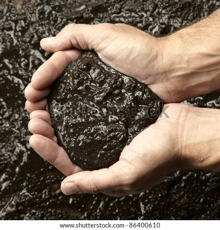 Closeup of hands holding mud - stock photo