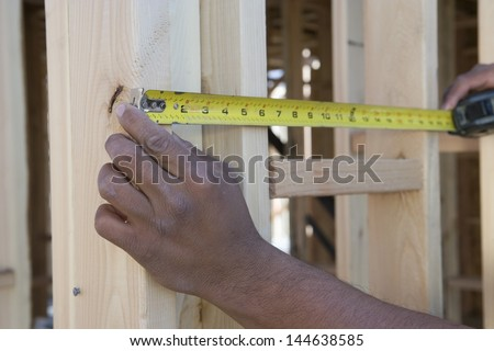 Closeup of hands measuring between boards with tape measure at construction site - stock photo