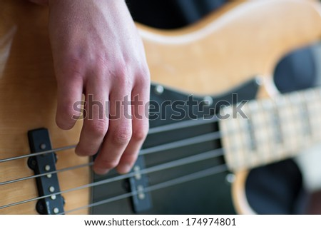 Closeup of hands of a man playing electrical bass guitar,with only his fingers in focus - stock photo