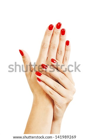 Closeup of hands of a young woman with long red manicure on nails. Isolated on white background