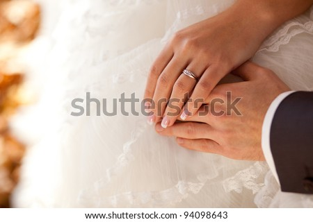 closeup of hands of bride and groom with wedding ring - stock photo