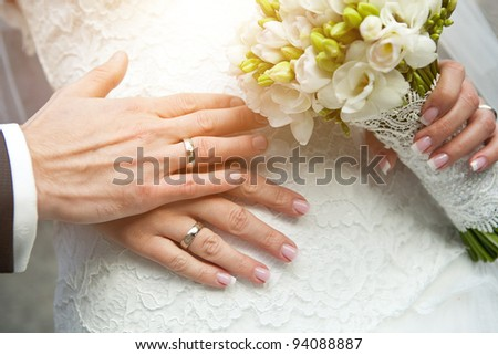 closeup of hands of bride and groom with wedding rings and bouquet - stock photo
