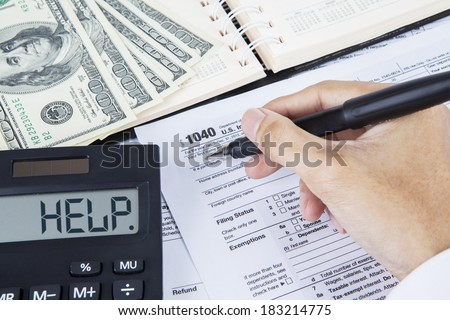 Closeup of hands of businessman filling tax form - stock photo