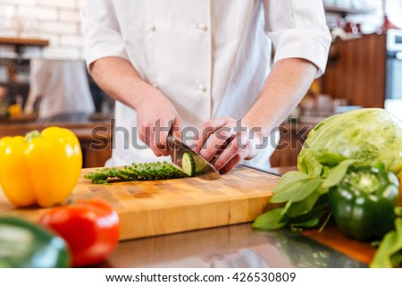 Closeup of hands of chef cook cutting fresh vegetables and making vegetarian salad on the kitchen