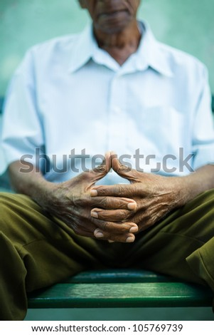 closeup of hands of elderly african american man sitting on bench - stock photo