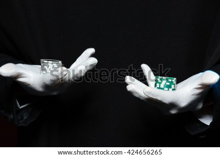 Closeup of hands of man magician in white gloves holding  casino chips on both palms over black background