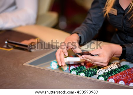 Closeup of hands of poker dealer with chips and cards in casino - stock photo