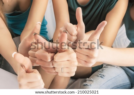 Closeup of Hands of Three Caucasian Females Showing Thumbs Up In Home Environment. Horizontal Image