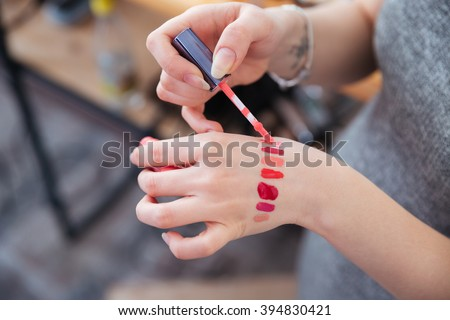 Closeup of hands of woman makeup artist testing lip gloss different colors on her hand - stock photo