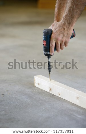 Closeup of Hands of Worker Using Drill - stock photo