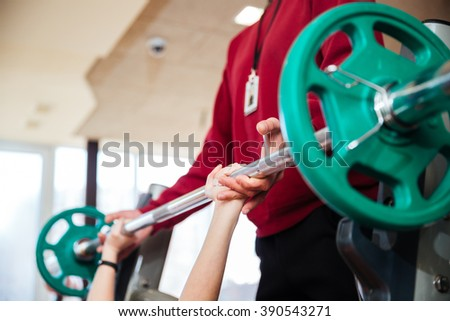 Closeup of hands of young sportswoman training with fitness instructor using barbell  in gym  - stock photo