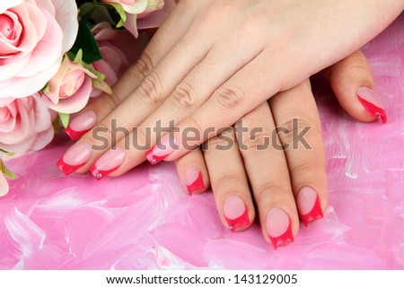 Closeup of hands of young woman with elegance manicure, on color background