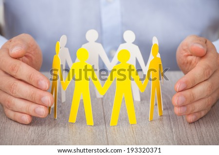 Closeup of hands protecting team of paper people on desk - stock photo