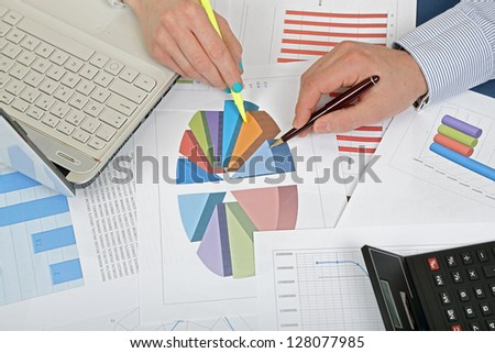 closeup of  hands while examining graphs - stock photo