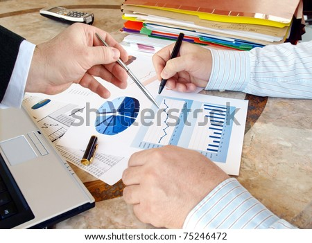 Closeup of hands with financial  charts  at business meeting in the office - stock photo