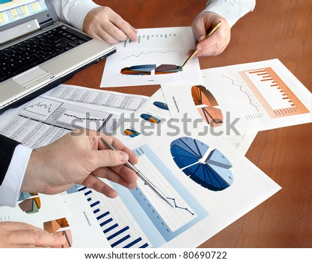 Closeup of hands with financial  charts  at business meeting in the office. - stock photo
