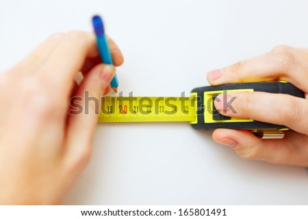 Closeup of hands with Measuring tape and pencil.