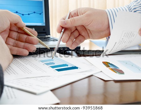 Closeup of hands with pens over the home sales chart - stock photo