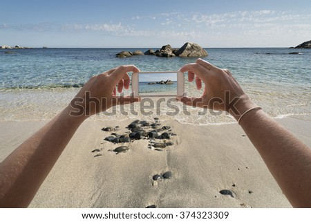 closeup of hands with phone that takes seaside scene - stock photo