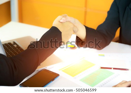 Closeup of handshake the businesswoman and businessman in the work office; select and soft focus.