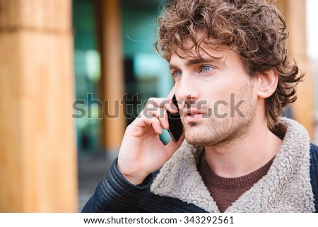 Closeup of handsome attractive serious concentrated curly young male talking on cellphone  - stock photo