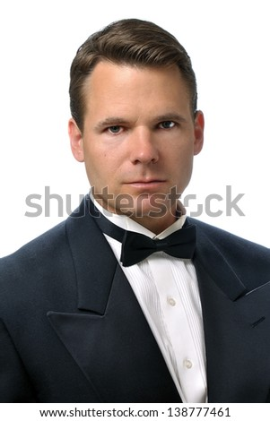 Closeup of handsome Caucasian man with serious expression wearing a black tuxedo on white background - stock photo