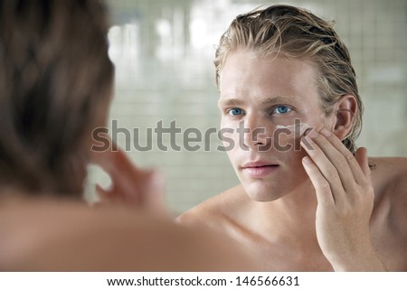 Closeup of handsome young man applying facial cream in front of mirror - stock photo