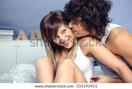Closeup of handsome young man kissing and doing tickles to beautiful woman laughing sitting over a bed. Love and couple relationships concept. - stock photo