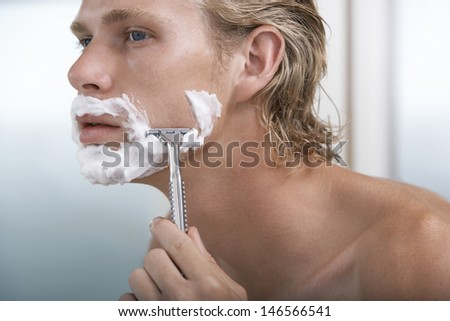 Closeup of handsome young man shaving in bathroom - stock photo