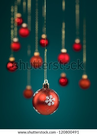 closeup of hanging christmas red globe decorated with snowflakes with golden threads on blue gradient background with blurred red globes - stock photo