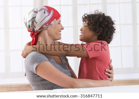 Closeup of happy  ill mother kissing her child boy - stock photo