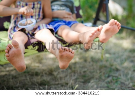 Closeup of happy kids sitting and swing on sunny countryside background. Picture of two children legs barefoot.  - stock photo