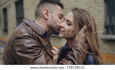 Closeup of happy loving couple kissing and embracing while havinhg walk in city street