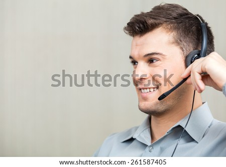 Closeup of happy male call center employee using headset while looking away at office - stock photo