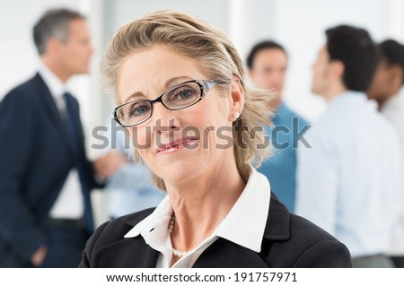 Closeup Of Happy Mature Businesswoman In Front Of Colleague - stock photo