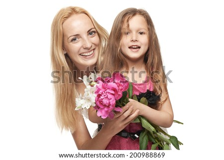 Closeup of happy mother and her daughter with bunch of flowers hugging, over gray background - stock photo