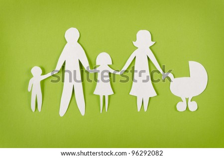 Closeup of happy paper family on green background - stock photo