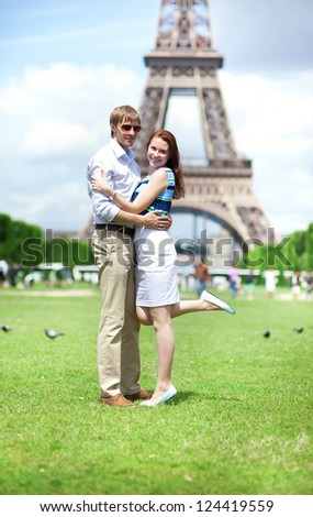Closeup of happy positive couple hugging near the Eiffel tower - stock photo