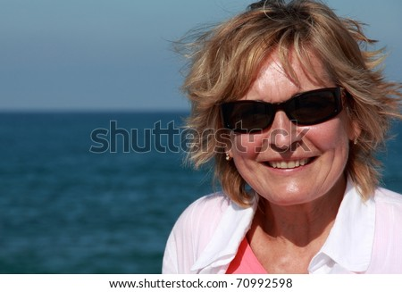 closeup of happy senior woman on beach
