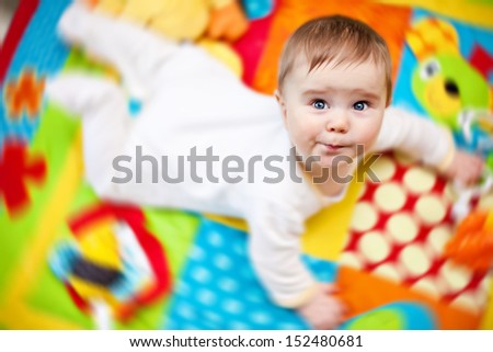 Closeup of happy six months baby boy crawling on colorful playmat - stock photo